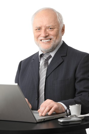 Portrait of happy senior businessman using laptop on coffee table, eye contact, white background. photo