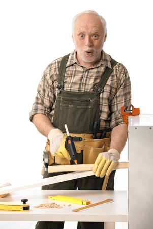 Elderly man working with tools, looking surprised, white background. Stock Photo - 6941519