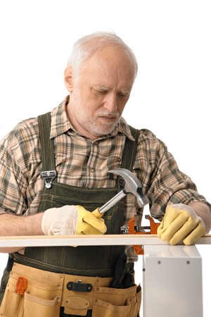 concentrating: Senior handyman concentrating on hammering, isolated on white.