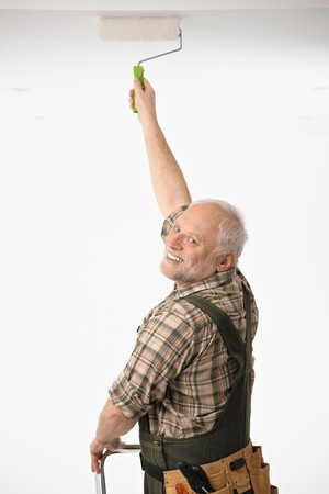 Elderly man painting the ceiling in white room. photo