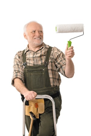one mature man only: Do it yourself home renovation, elderly man standing on ladder painting wall.