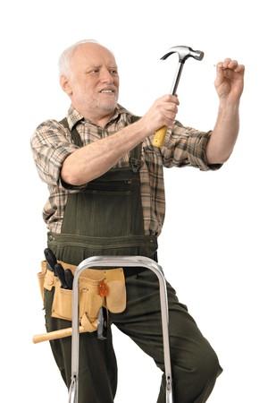 Gli anziani tuttofare facendo domestico di rinnovamento martellare chiodo, sfinestratura.