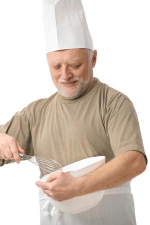 Senior chef whisking egg in kitchen, white background. photo