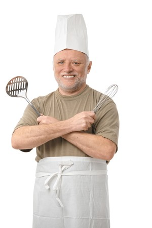 Portrait of senior man posing with cooking utensils, smiling. photo
