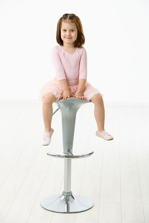 Portrait of happy little girl wearing ballet costume sitting on high chair against white background, looking at camera, smiling. photo
