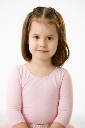 Portrait of smiling little girl in pink dress over white background. photo