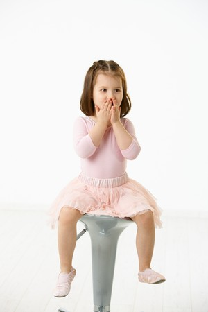 little girl sitting: Portrait of happy little girl wearing ballet costume sitting on high chair against white background, looking surprised.