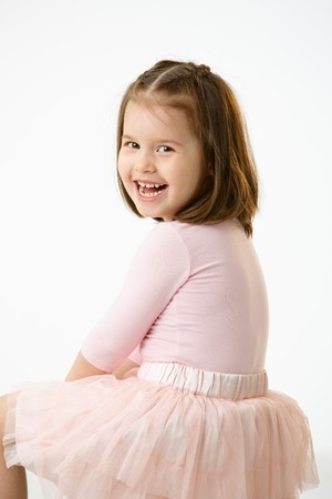 Portrait of happy little girl (4-5 years) wearing ballet costume looking back at camera, laughing. Studio shot over white background. photo