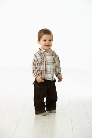 2 to 3 years: Full size ritratto di bambino carino (2-3 anni) in abiti casual, guardando la fotocamera, sorridente. Foto su sfondo bianco.