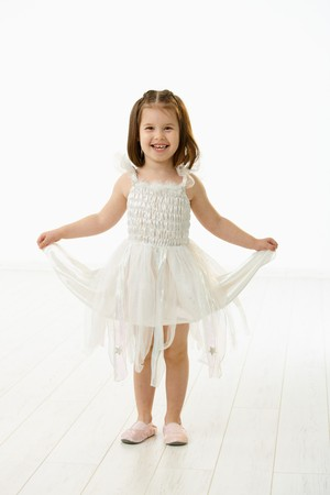 preschoolers: Full length portrait of cute little girl (4-5 years) wearing ballet costume looking at camera, smiling. Studio shot over white background. Stock Photo