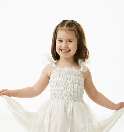 Portrait of happy little girl (4-5 years) wearing ballet costume looking at camera, smiling. Studio shot over white background. photo