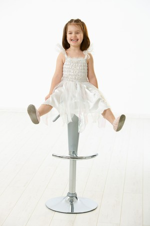rozkošný: Portrait of cute little girl (4-5 years) wearing ballet costume laughing. Studio shot over white background.
