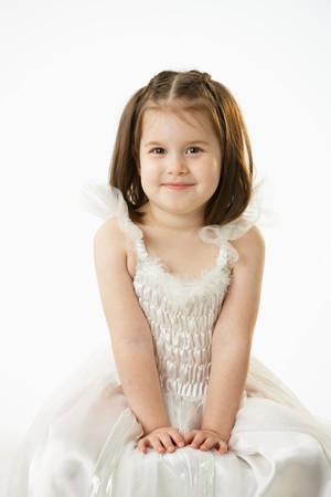 Portrait of cute little girl (4-5 years) wearing ballet costume looking at camera, smiling. Studio shot over white background. photo