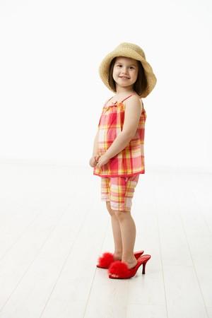 big five: Piccola figlia cercando scarpe grandi madri, guardando alla fotocamera, sorridente. Studio girato su sfondo bianco.