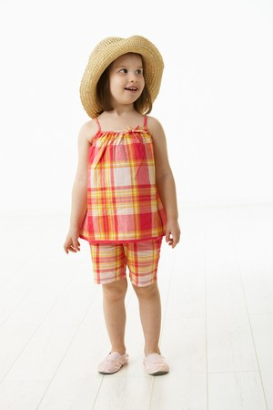 Portrait of cute little girl (4-5 years) wearing summer dress and straw. Studio shot over white background. photo