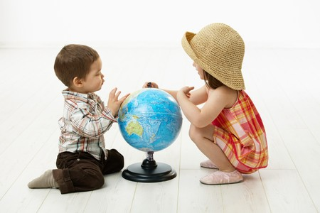 3 4 length: Little kids crouching on floor playing with globe over white background.