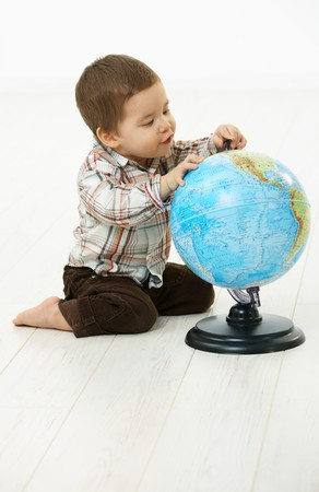 Cute little kid (2-3 years) sitting on floor playing with globe over white background. photo