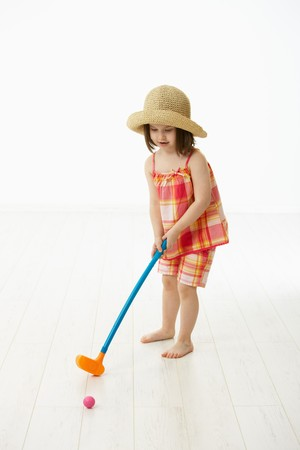 Little girl (4-5 years) in summer dress and straw playing golf indoor. White background. Stock Photo - 6927319