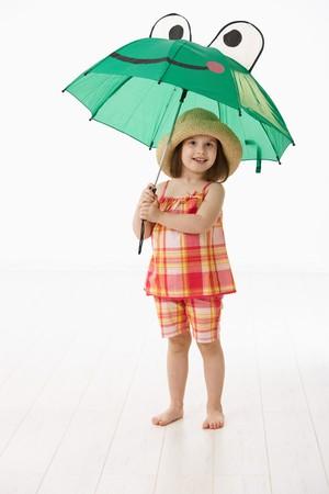 愉快的小女孩(4-5岁)在拿着在白色背景的夏天礼服和秸杆的伞。