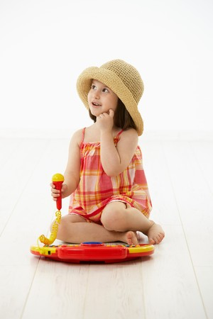 Little girl sitting on floor playing with toy music instrument, daydreaming over white background. photo