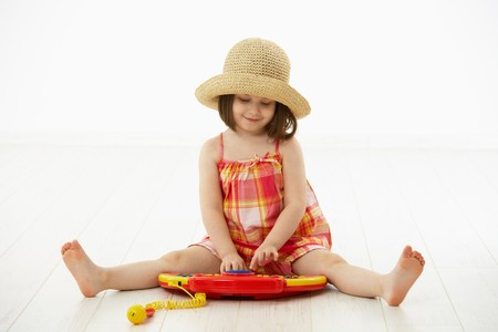 Little girl sitting on floor playing with toy music instrument, daydreaming over white background. Stock Photo - 6941514
