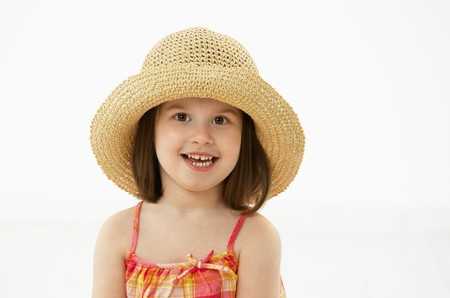 Portrait of cute little girl (4-5 years) wearing summer dress and straw, looking at camera. Studio shot over white background. photo