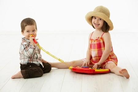 ni�o cantando: Ni�os felices jugando en instrumento de m�sica de juguete, ni�o cantando para micr�fono sobre fondo blanco. Foto de archivo