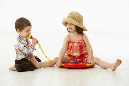 3 4 length: Happy kids playing on toy music instrument, little boy singing to microphone over white background.