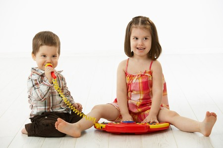 Happy kids playing on toy music instrument, little boy singing to microphone over white background. Stock Photo - 6927313