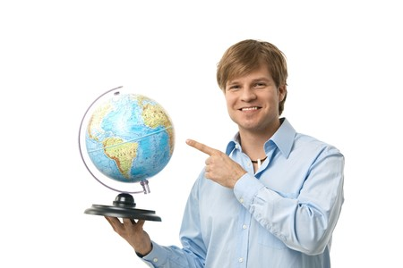 Happy young man pointing to globe in his hand, smiling. Cutout. photo