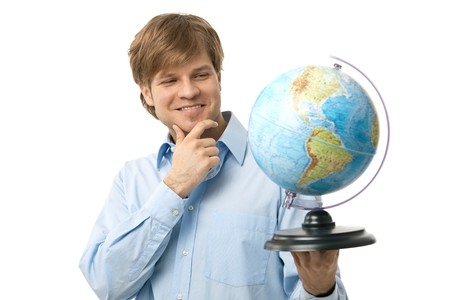 Portrait of young traveler, holding globe in hand, thinking on his next destination. Isolated on white. photo