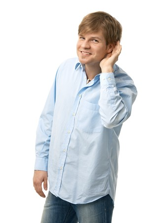 satisfied people: Portrait of happy young man listening, holding hand to his ear. Isolated on white.