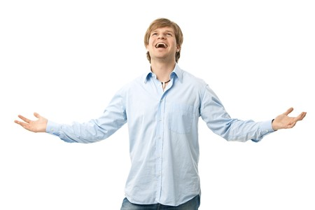 arms wide: Happy young man standing with arms wide open, laughing. Isolated on white.