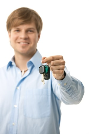handing: Young man handing over ignition keys. Selective focus on keys, isolated on white.
