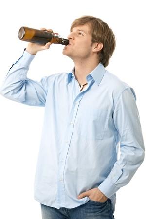 man drinkt bier: Casual jonge man Drink flesje bier. Op wit wordt geïsoleerd.  Stockfoto