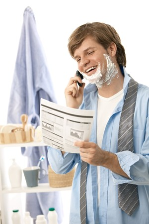 Young man reviewing document and talking on mobile while shaving in the morning. Isolated on white photo