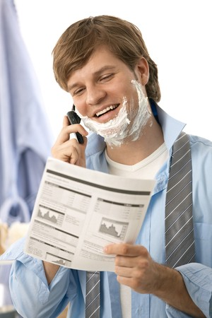 financials: Young man reviewing document and talking on mobile while shaving in the morning. Isolated on white