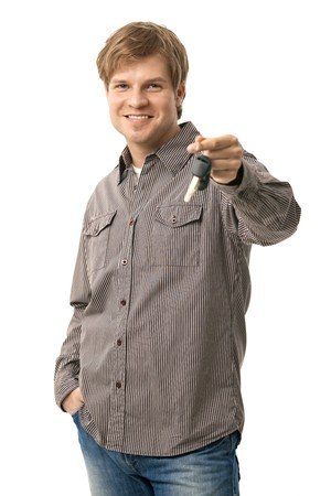Casual young man holding ignition keys, smiling. Isolated on white. Stock Photo - 6925827