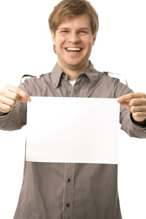 Casual young man holding blank sheet of paper, smiling. Isolated on white, selective focus on paper. Stock Photo - 6942979