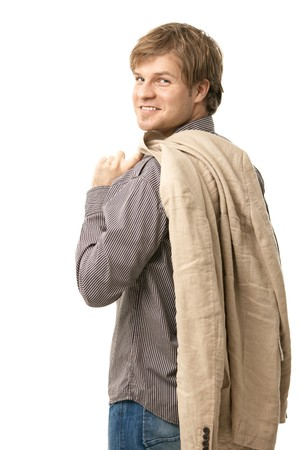 looking over shoulder: Portrait of trendy young man, standing with jacket over shoulder. Isolated on white. Stock Photo