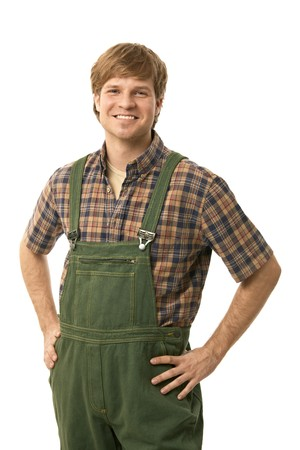 Confident young worker wearing green workwear, standing with arms on hips, smiling. Cutout. photo