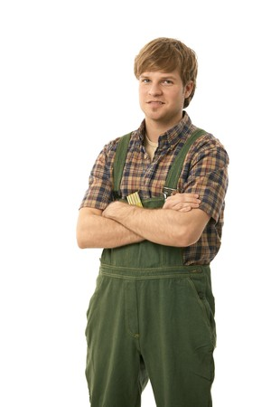 Portrait of young handyman wearing green workwear, standing arms crossed. Isolated on white. photo
