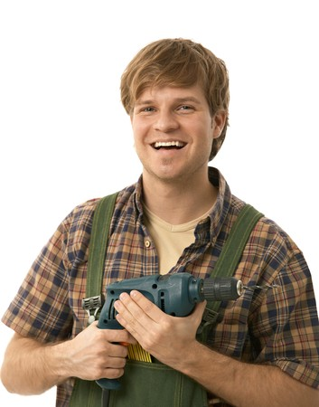 journeyman: Young handyman holding power drill, smiling. Isolated on white.