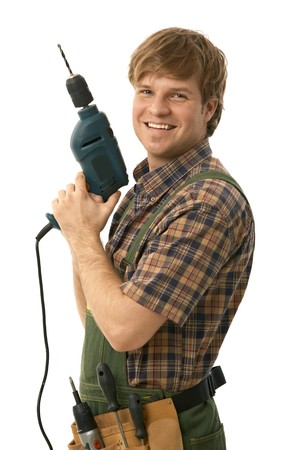toolset: Happy handyman posing with power drill, smiling. Isolated on white.