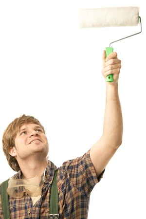 Young man painting wall using paint roller, smiling. Isolated on white. photo
