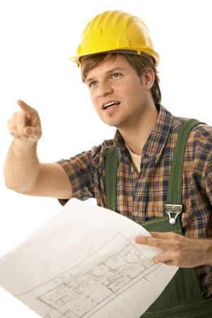 Worried builder holding floor plan, pointing to some problem. Isolated on white. photo