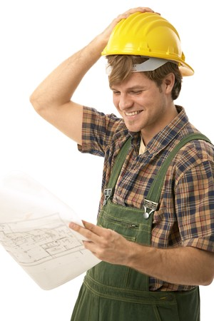 Confident handyman in hardhat, looking at floor plan, smiling. Isolated on white. photo