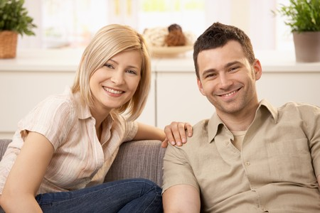 Smiling couple sitting on couch in sunny living room. photo
