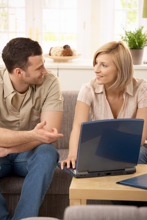chat room: Smiling couple sitting at home in discussion, using laptop.