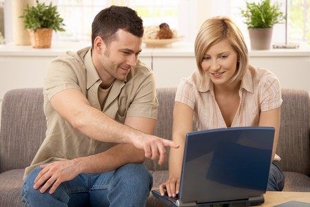 Young man pointing at laptop computer screen, pretty girlfriend smiling. photo
